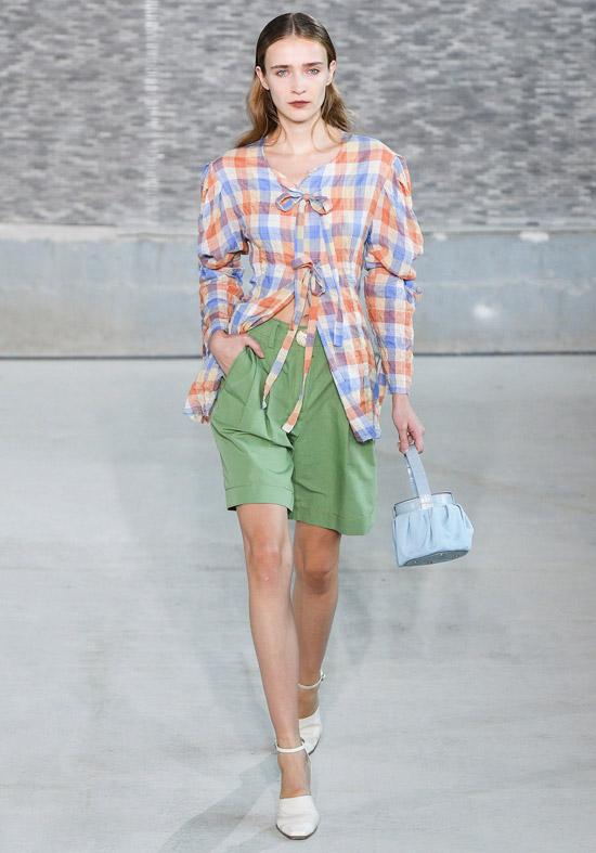 Модель в зеленых шортах, рубашка в клетку и туфли