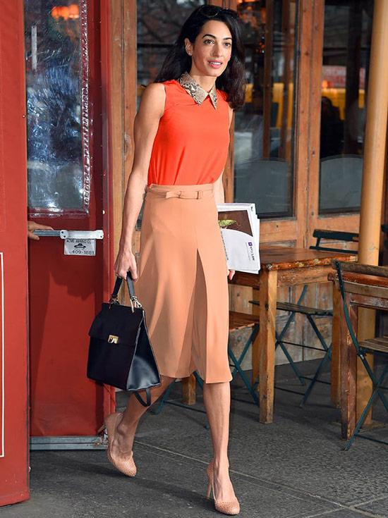 Амаль Клуни в оранжевом топе, персиковая юбка миди, черная сумка