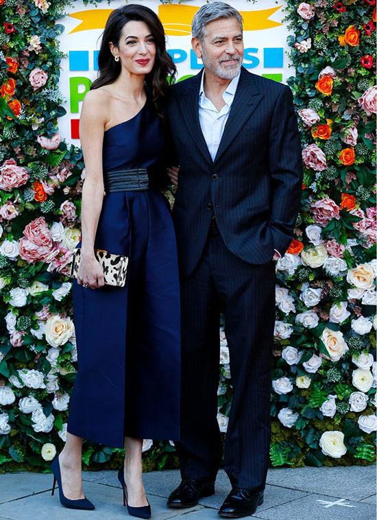 Амаль Клуни в темно синем комбинезоне с черным поясом и туфли на шпильке