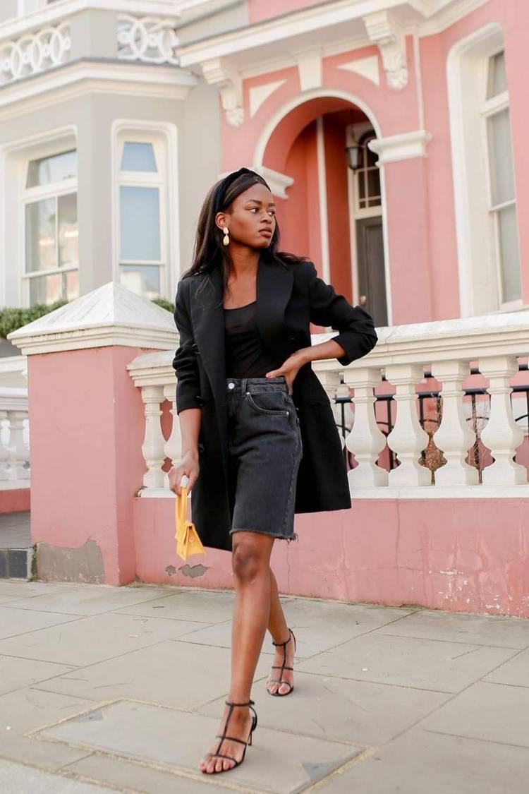 Девушка в джинсовых бермудах, черный удлиненный кардиган и босоножки с ремешками