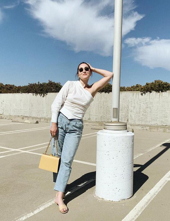 Девушка в голубых прямых джинсах и топ на одно плечо