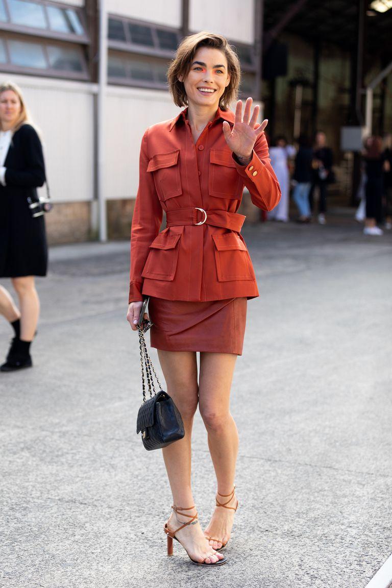 Девуша в мини юбке, блейзер с поясом и коричневые босоножки на ремешках