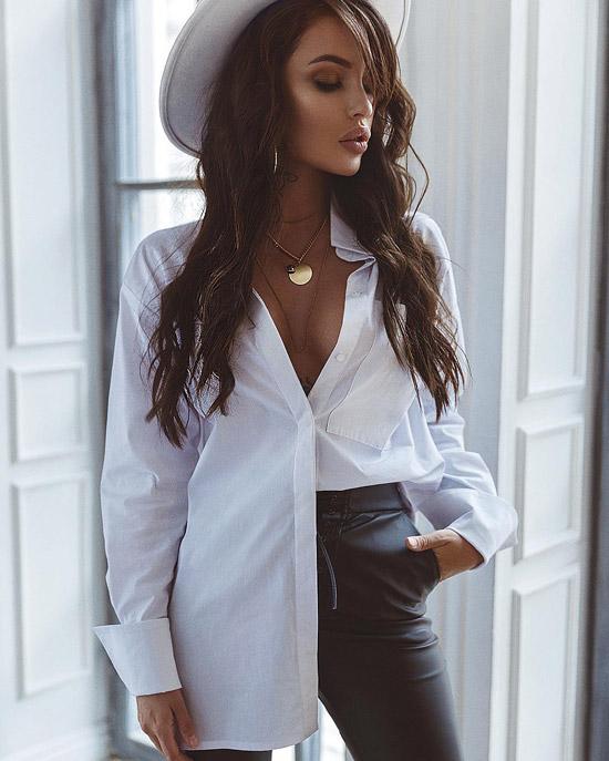 Девушка в асимметрино заправленной блузке оверсайз, кожаных брюках и шляпе