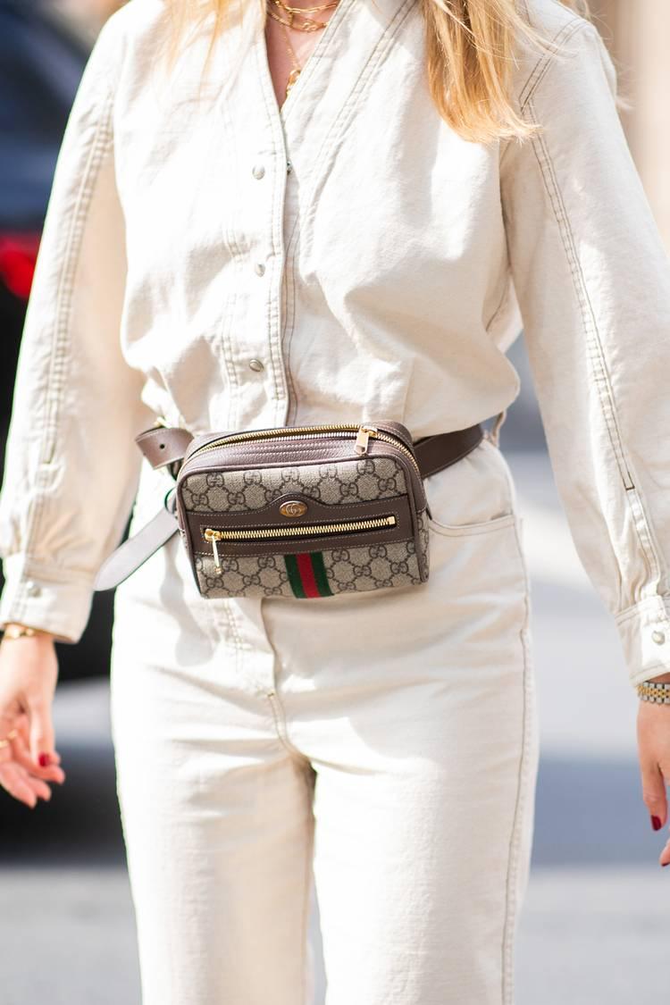 Девушка в белом брючном костюме и поясная сумка