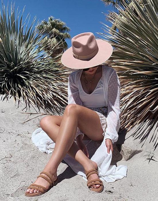 Девушка в белой пляжной накидке, бежевая шляпа и сандалии