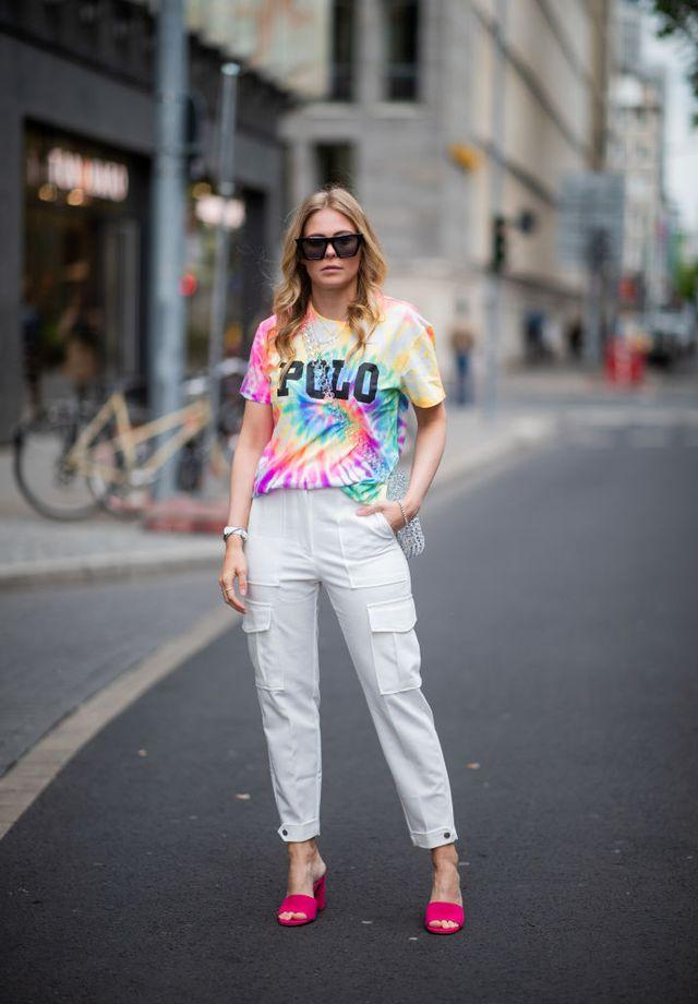Девушка в белых брюках, футболке с принтом и ярких босоножках