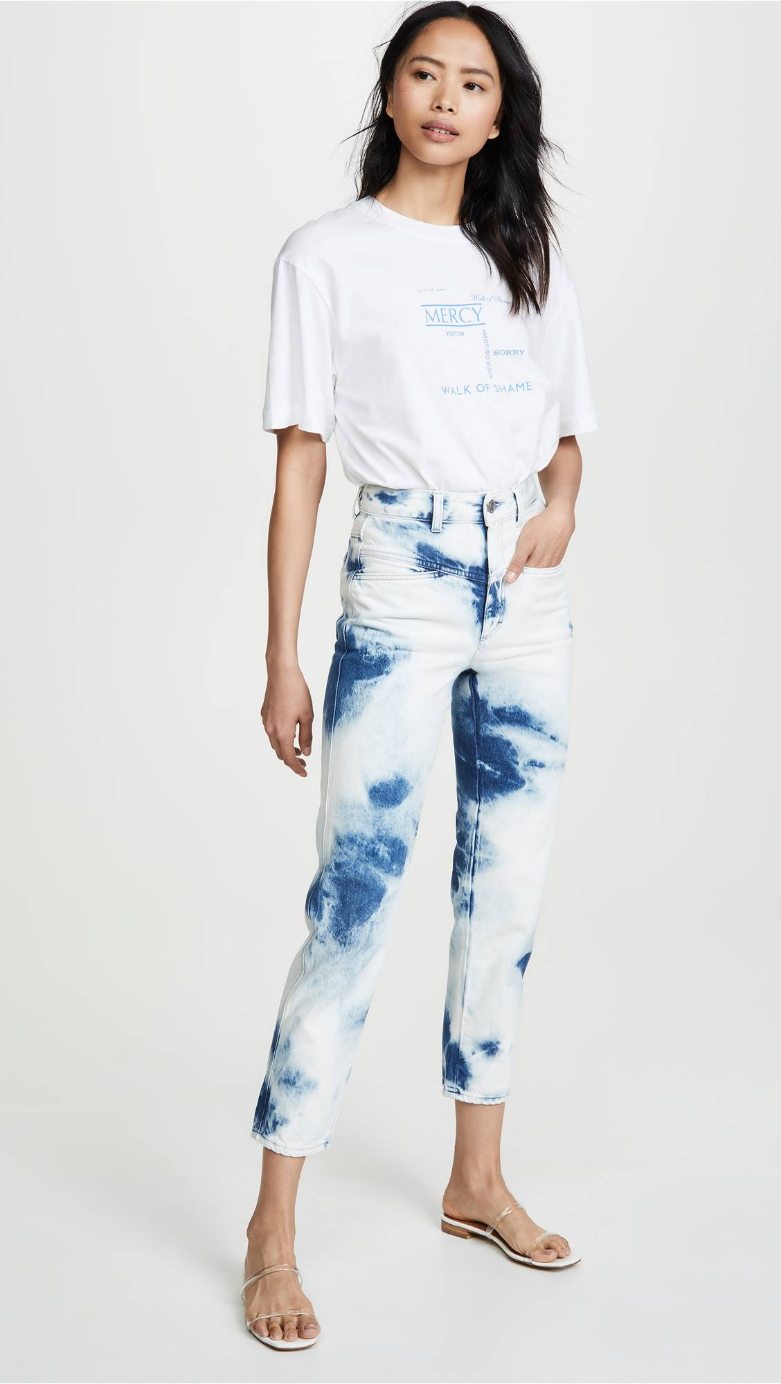 Девушка в беой футболке и укороченных джинсах
