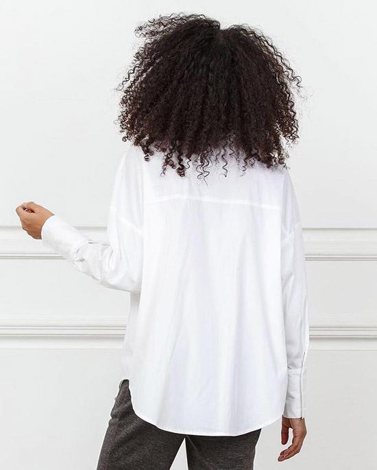 Девушка в бузке оверсайз и брюках стоит спиной