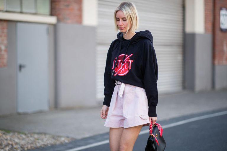 Девушка в черном свитшоте и розовых шортах