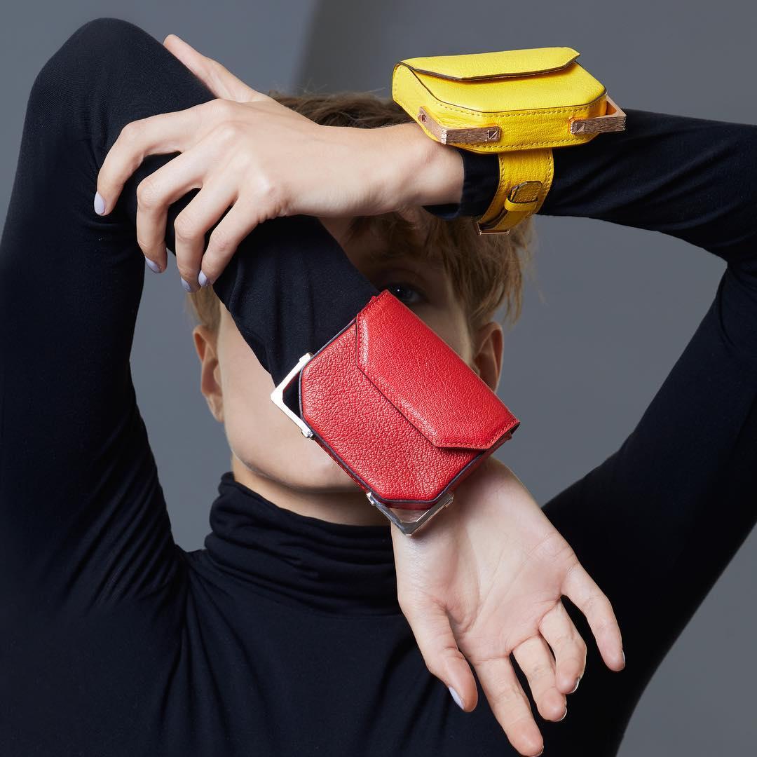 Девушка в черной водолазке и красная наручная сумочка
