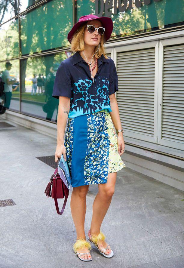 Девушка в голубой юбке выше колен, рубашка с принтом и шляпа