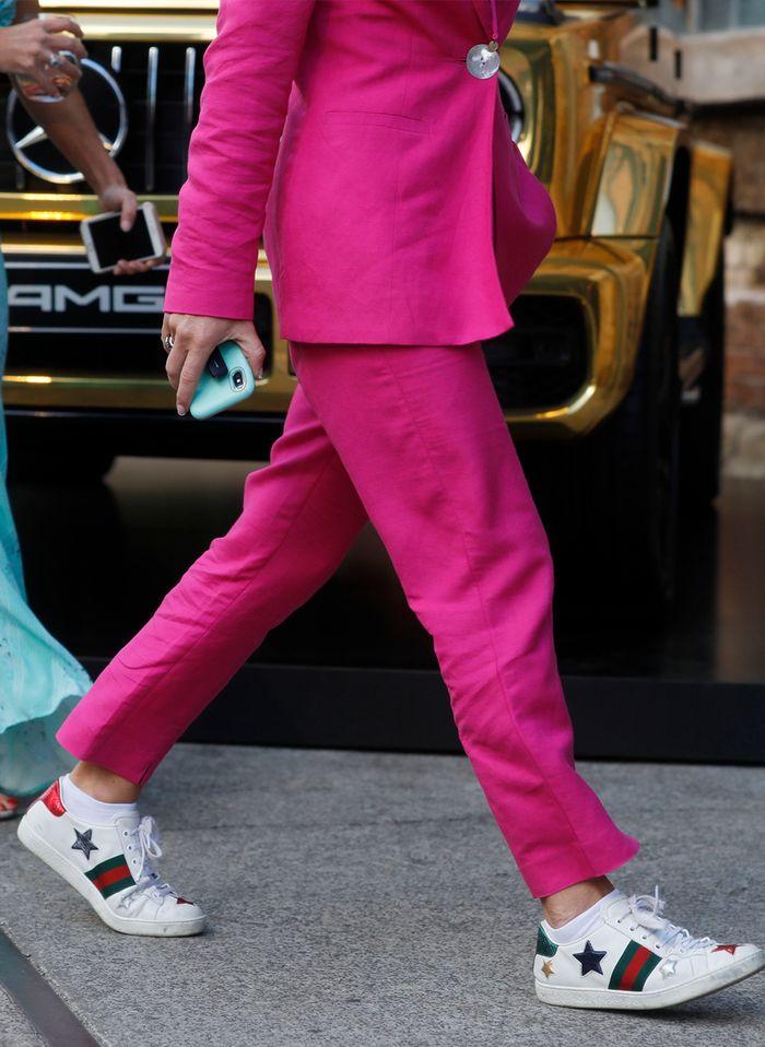 Девушка в костюме с брюками цвета фуксии и белые кеды