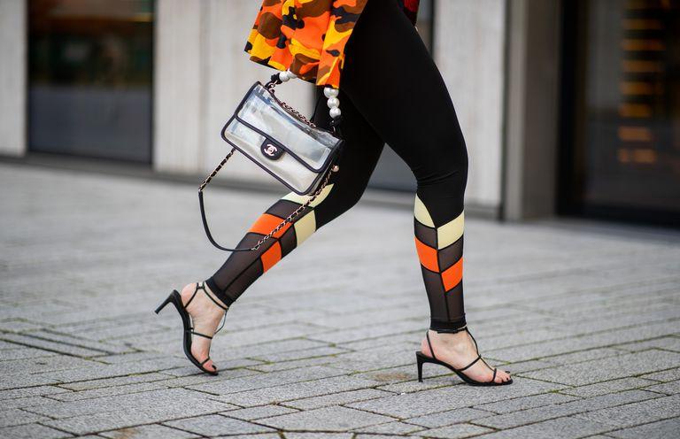 Девушка в леггинсах и черных босоножках на низком каблуке
