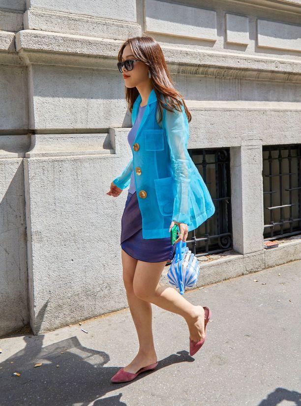 Девушка в мини юбке, голубой жакет и туфли на плоской подошве