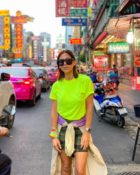 Девушка в неоново желтой футболке, велосипедные шорты и солнцезащитные очки
