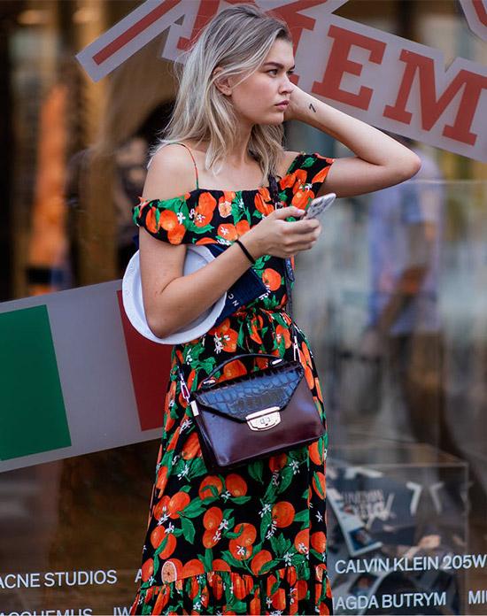 Девушка в платье с принтом томатов и текстурированной сумочкой
