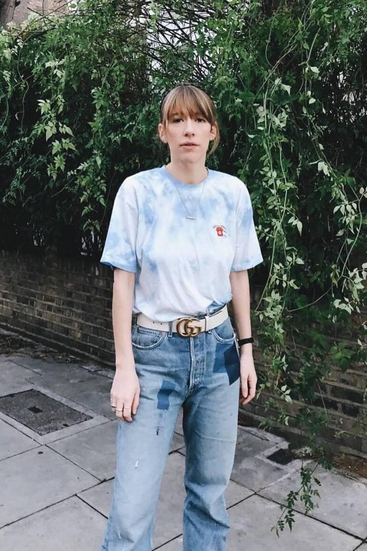 Девушка в простой футболке, голубые джинсы и ремень