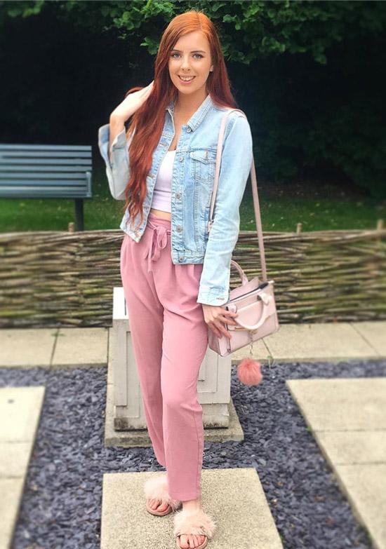 Девушка в розовых брюках, белый кроп топ и голубая джинсовая куртка