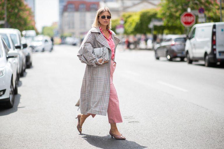 Девушка в розовых брюках, блузе и плаще в клетку