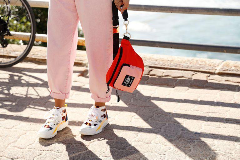 Девушка в розовых подвернутых джинсах и кроссовках