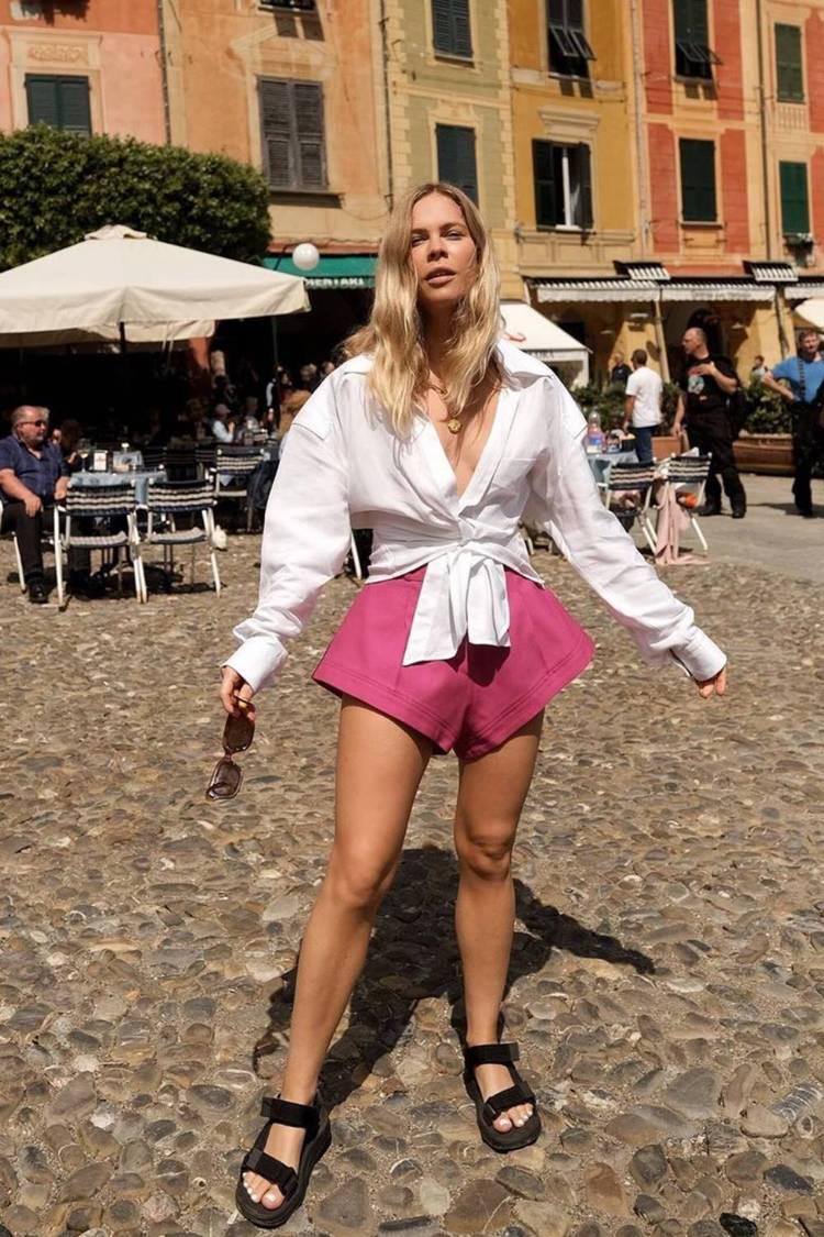 Девушка в розовых шортах мини, белая рубашка с рукавами и черные сандалии