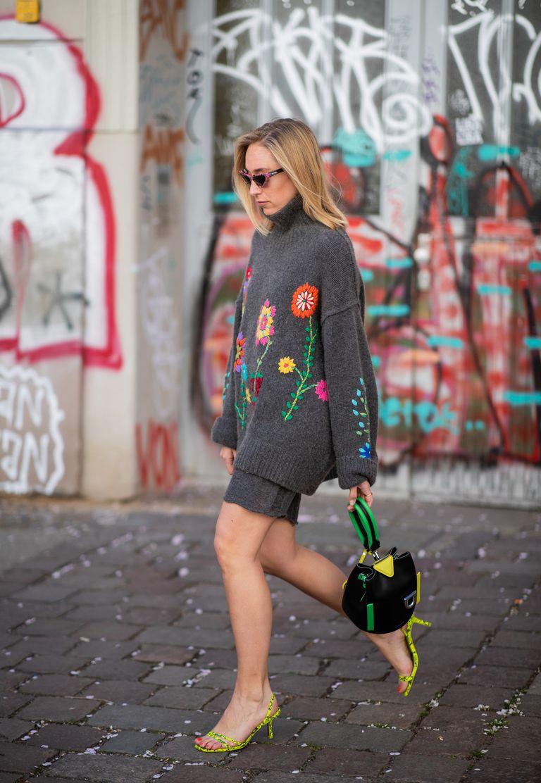 Девушка в сером свитере оверсайз с вышевкой и зеленые босоножки на низком каблуке