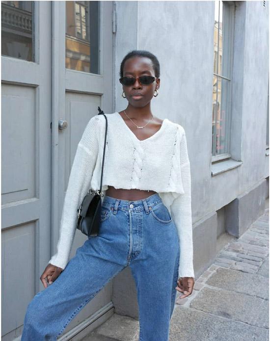 Девушка в свободных джинсах и белой укороченной блузке с рукавами