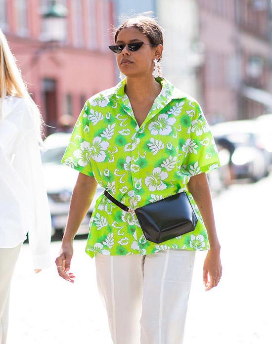 Девушка в яркой рубашке с тропическим принтом и белых брюках