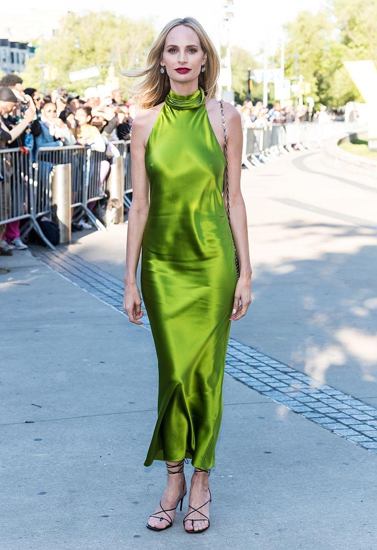 Девушка в зеленом шелковом платье и черных босоножках с ремешками
