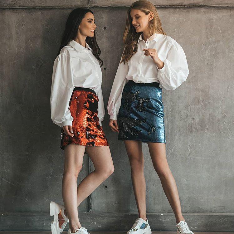 Девушки в блузках оверсайз, разноцветных юбках и кроссовках