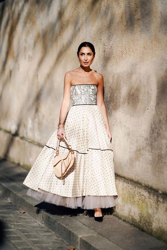 Девушка в легком летнем платье в горошек и бежевая сумочка