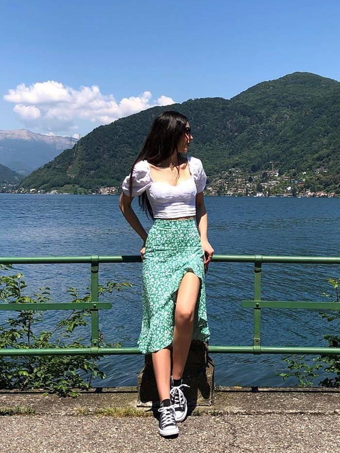 Девушка в укороченной блузке, зеленая юбке миди и черные кеды