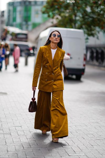Девушка в бархатном костюме с широкими брюками и мини сумочка