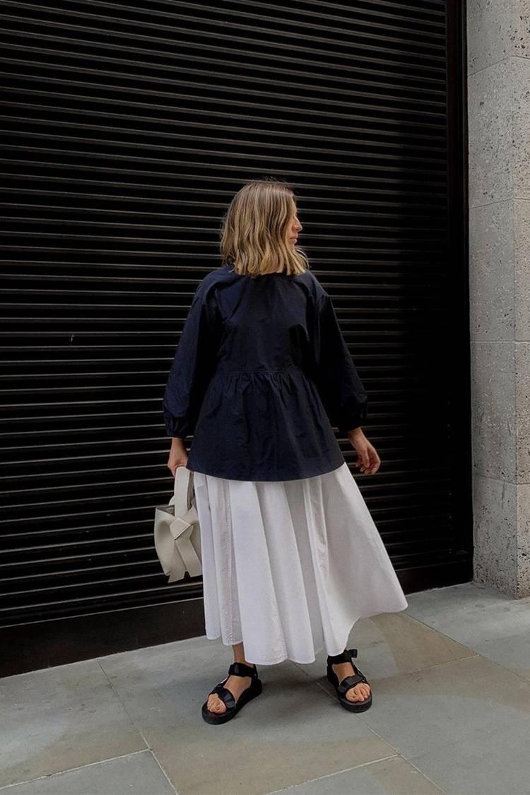 Девушка в белой юбке миди, черная блуза и черные сандалии