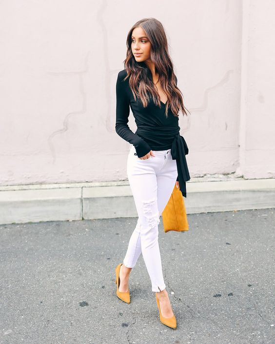 Девушка в белых джинсах, черная блузка и желтые туфли