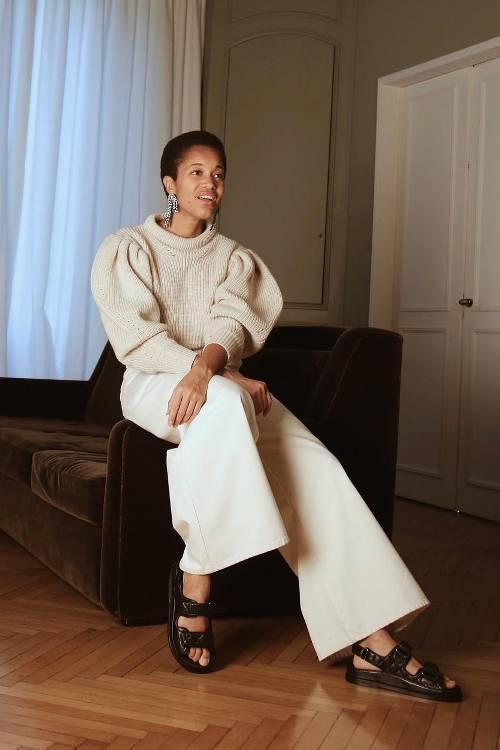 Девушка в белых широких брюках, свитер и черные сандалии