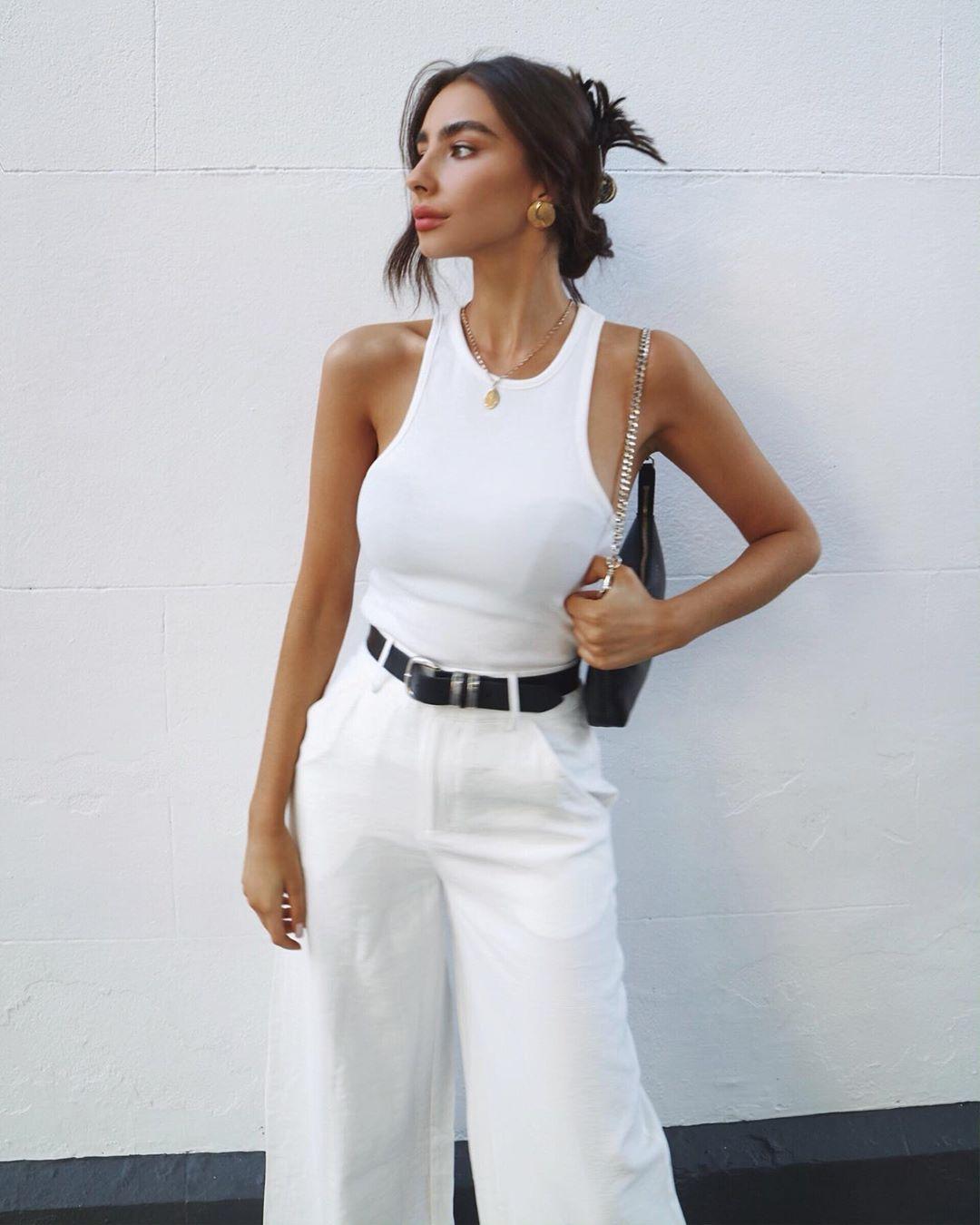Девушка в белых широких джинсах с черным ремнеи и простой белой майке
