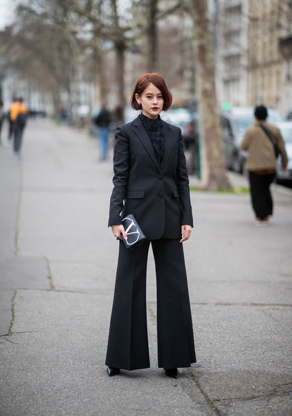 Девушка в черном костюме с брюками клеш, водолазка и мини клатч