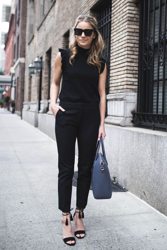 Девушка в черных брюках, топе и босоножках