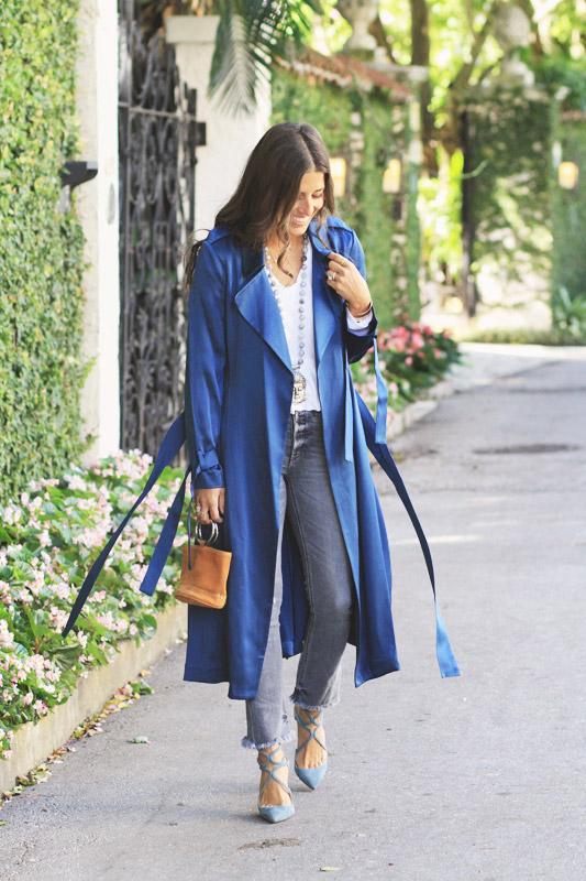 Девушка в джинсах скинни, синий плащ с поясом и голубые туфли