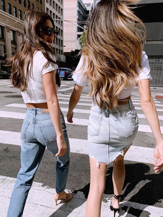Девушка в голубых джинсах с завышенной талией и укороченная футболка
