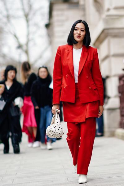 Девушка в красном брючном костюме, белые ботильоны и сумочка