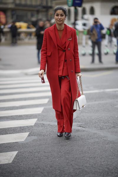 Девушка в красном брючном костюме, пальто и белая сумочка