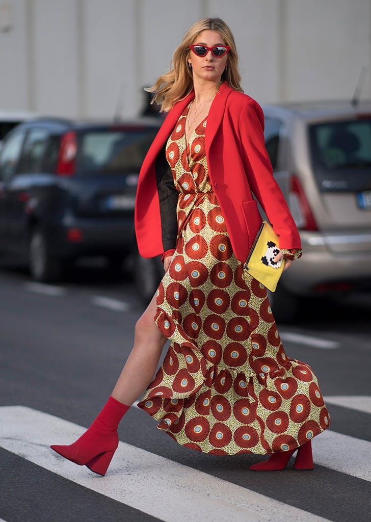 Девушка в легком платье макси с принтом, красный блейзер и ботильоны