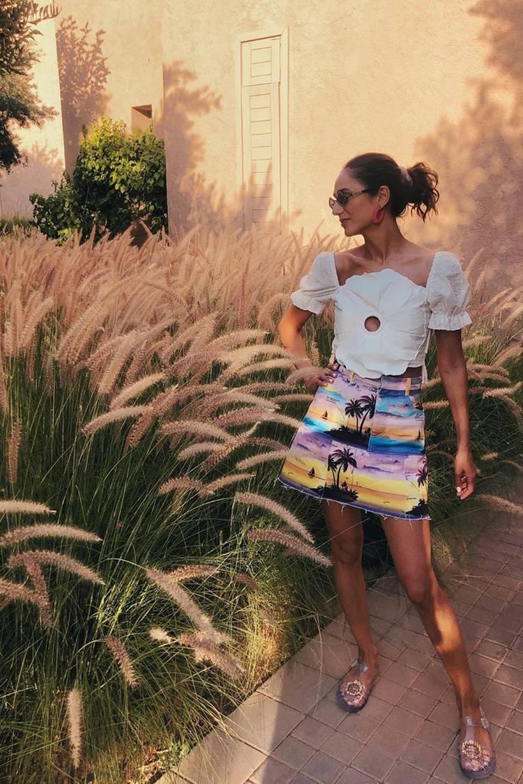 Девушка в летней мини юбке, белый топ и сандалии на плоской подошве