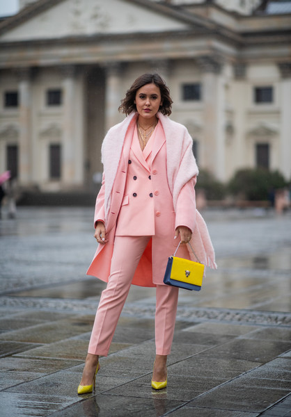 Девушка в нежно розовом костюме, пальто и желтые туфли и клатч