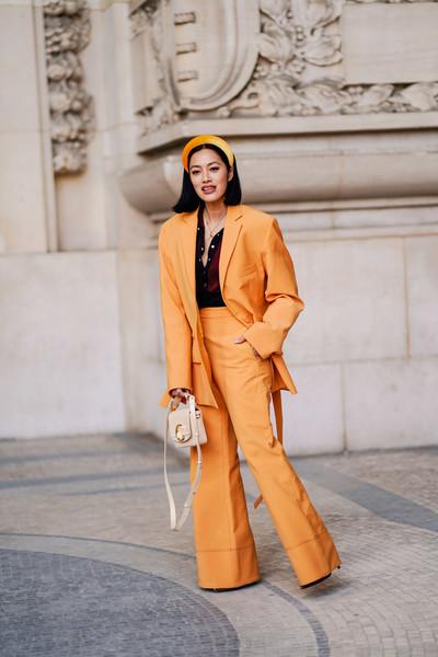 Девушка в оранжевом брючном костюме, ободок и сумочка