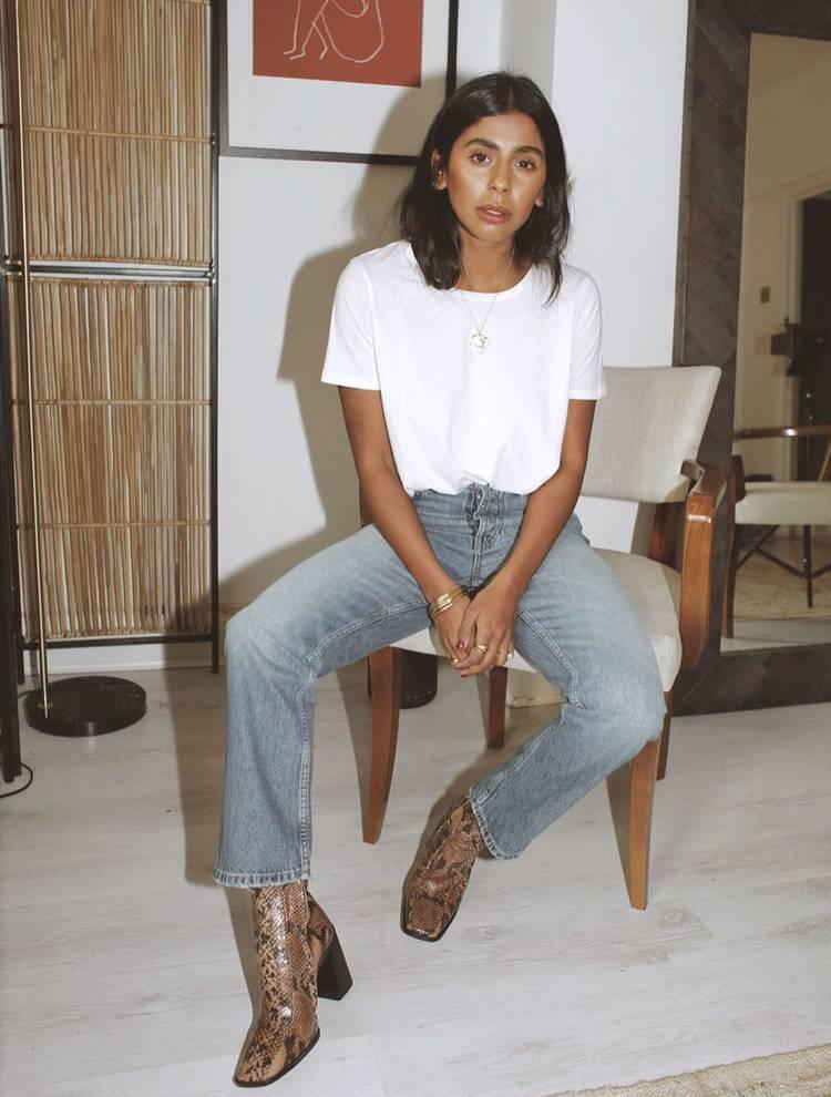 Девушка в прямых джинсах, белая футболка и сапоги из змеиной кожи