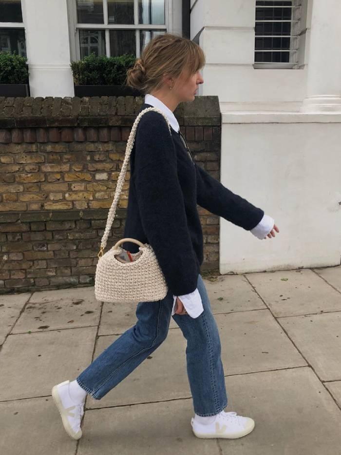 Девушка в прямых джинсах, черный джемпер и белые кеды