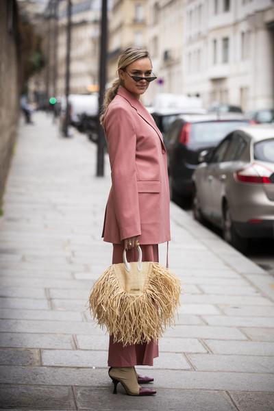 Девушка в розовом костюме, соломенная сумка и ботильоны